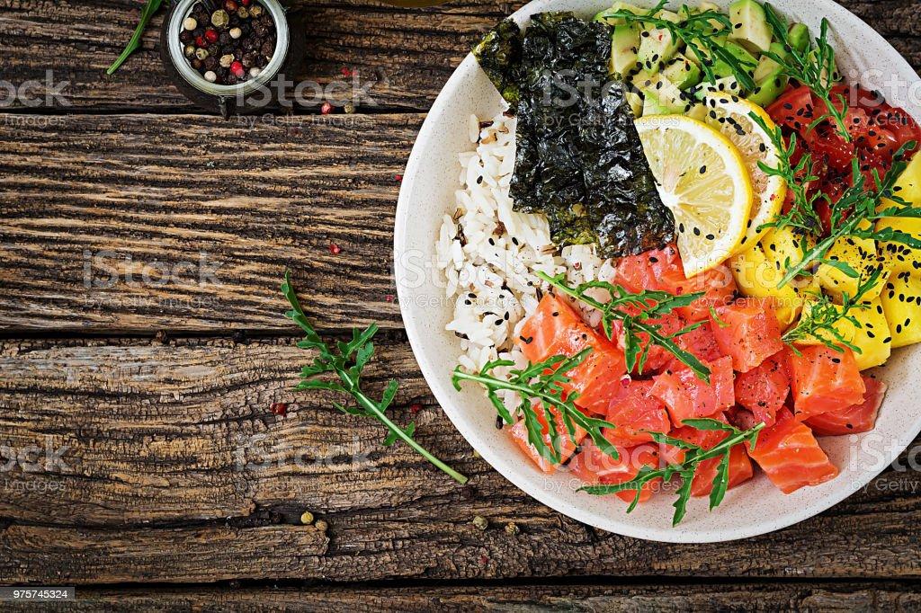 Hawaiian Lachs Fisch Poke Schüssel mit Reis, Avocado, Mango, Tomaten, Sesam und Algen. Buddha-Schüssel. Diätkost. Ansicht von oben. Flach zu legen - Lizenzfrei Avocado Stock-Foto