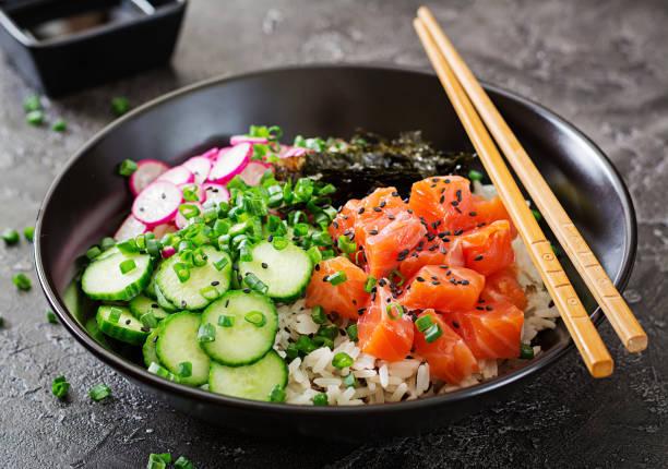 夏威夷鮭魚魚戳碗與大米, 蘿蔔, 黃瓜, 番茄, 芝麻種子和海藻。佛碗。飲食食品 - 沙律碗 個照片及圖片檔