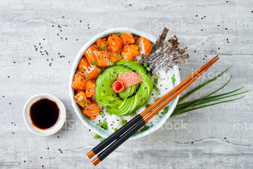 Hawaiian salmon poke bowl with seaweed, avocado rose, sesame seeds and scallions. Top view, overhead, flat lay, copy space stock photo