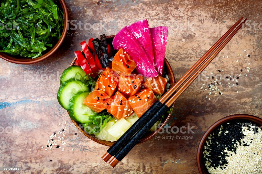 Hawaiian salmon poke bowl with seaweed, watermelon radish, cucumber, pineapple and sesame seeds. Copy space background, overhead, flat lay stock photo