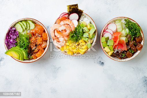 istock Hawaiian salmon, tuna and shrimp poke bowls with seaweed, avocado, mango, pickled ginger, sesame seeds. Top view, overhead, flat lay 1034587162