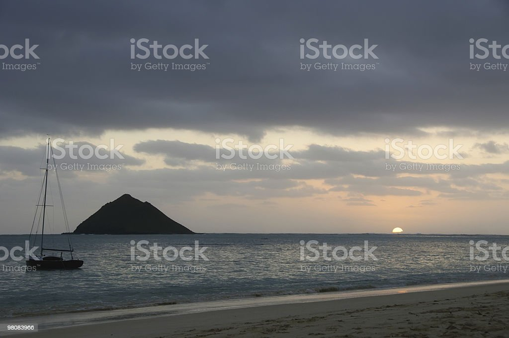 Hawaiian alba con isola al largo e barca a vela foto stock royalty-free