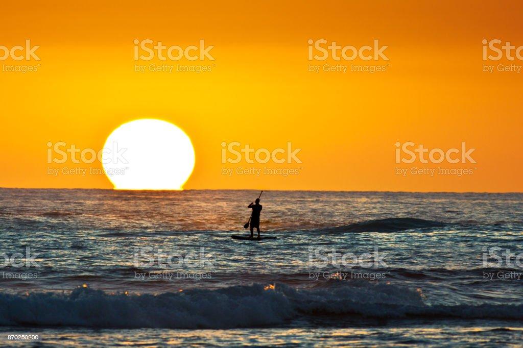 Hawaiian Sunset with Paddle Board Surfer at Poipu Beach Kauai stock photo