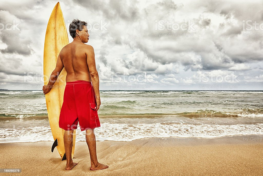 Hawaiian Surfer Standing on Beach with Surfboard stock photo