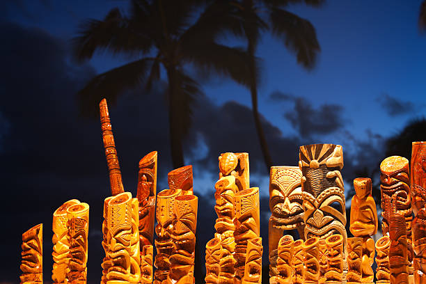 Hawaiian tiki mask art and blue palm tree sky. Poipu, Hawaii, USA - Jan 7, 2011: Hawaiian tiki carved artwork presented for sale by a local artist during a Luau. big island hawaii islands stock pictures, royalty-free photos & images