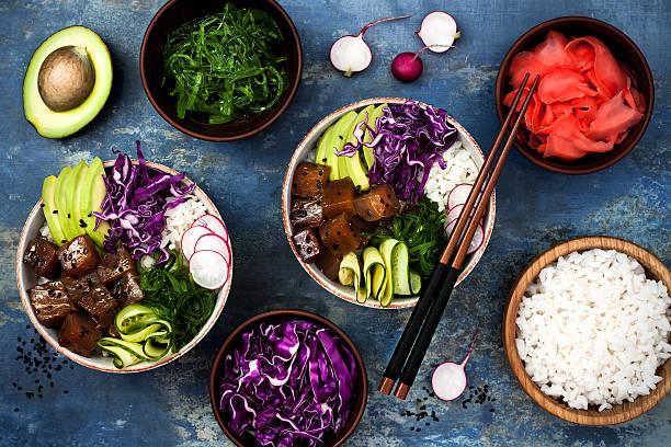 hawaiian tuna poke bowl with seaweed, avocado, red cabbage, radishes - hawaiianischer salat stock-fotos und bilder