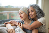 Hawaiian woman in 50s embracing her mid-20s daughter on couch who is fighting cancer