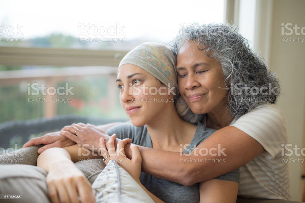 Hawaiian woman in 50s embracing her mid-20s daughter on couch who is fighting cancer stock photo