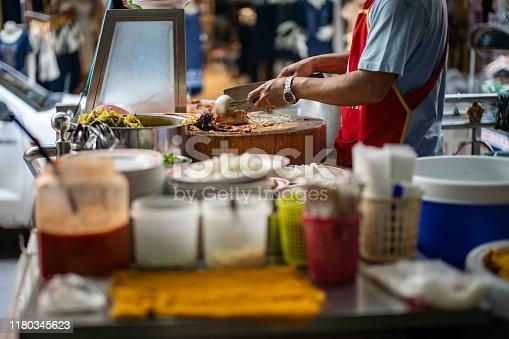 Hawker preparing Thai style stewed pork leg meal on street