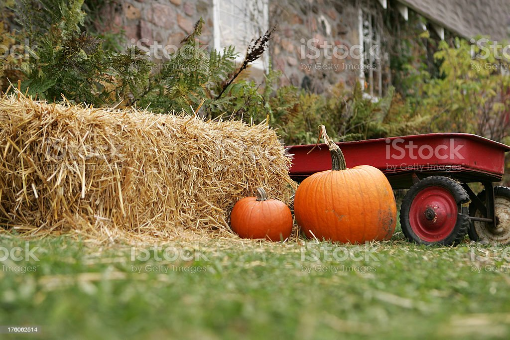 Hay Bale, Pumpkins and Red Wagon with Stone Barn Background stock photo