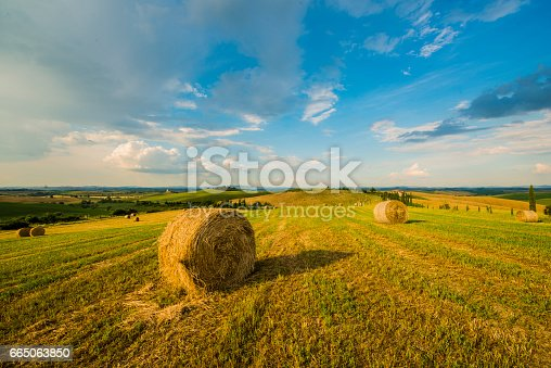 Hay bales on agricultural field. Scenic view of hilly landscape against sky. Idyllic view of nature in Italy.