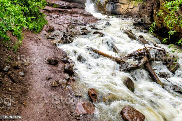 Photo of Hays creek falls waterfall trail in Redstone, Colorado during summer with raging river water from snowmelt flood and red rocks long exposure