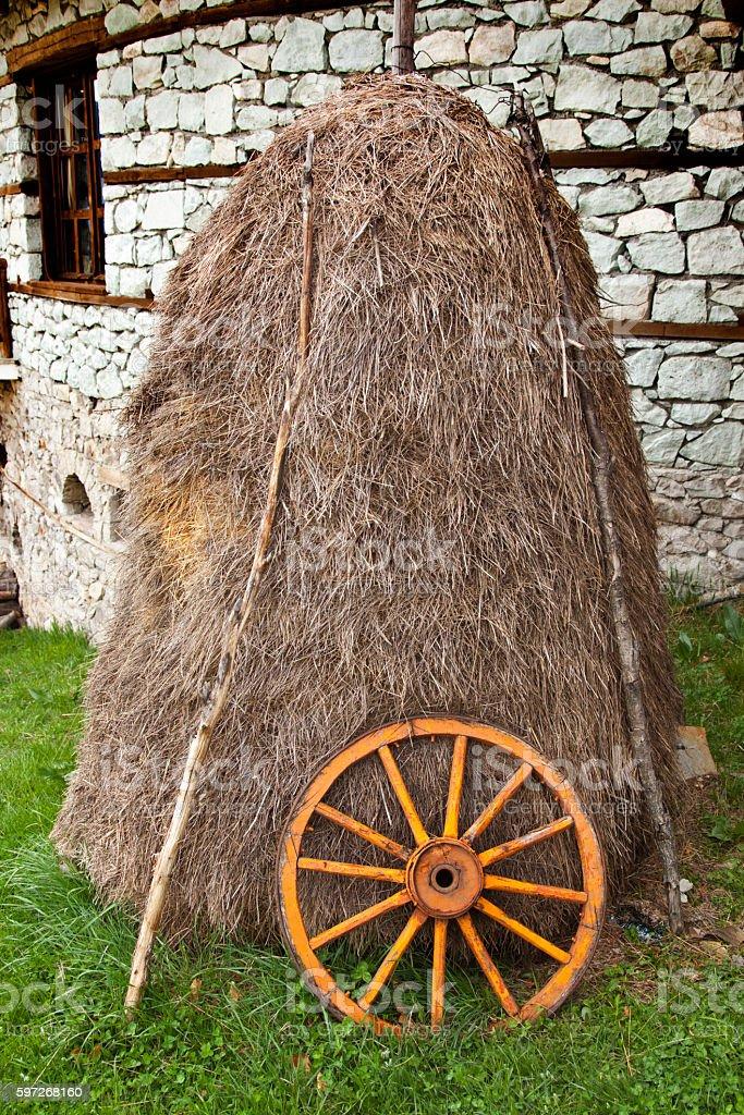 haystack and wagon wheel in a farmyard Lizenzfreies stock-foto