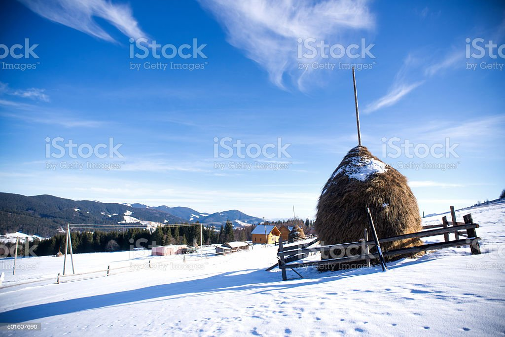 Haystack at dawn in winter mountains stock photo