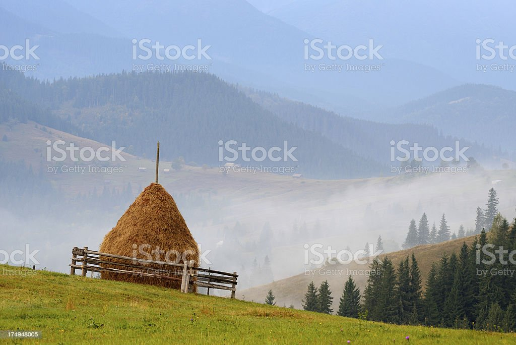 Haystack in morning misty mountains royalty-free stock photo