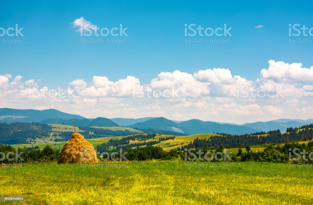 haystack on a grassy field on top of a hill stock photo