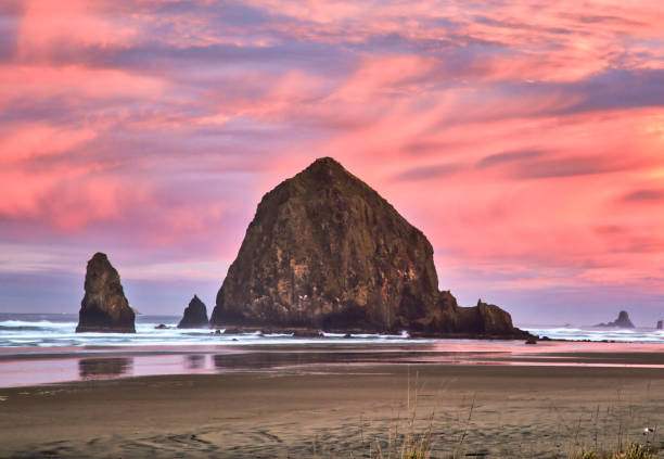 Haystack Rock in Cannon Beach at Dawn with watercolor sunrise stock photo