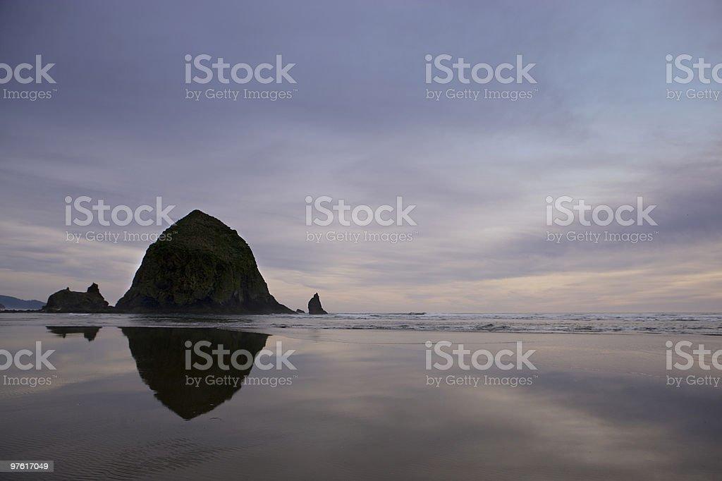Haystack Rock Oregon reflection on sand royalty-free stock photo