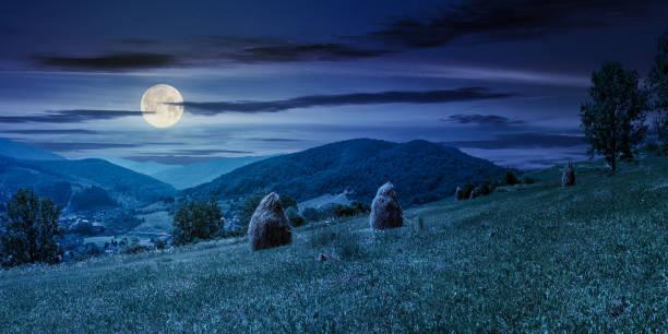 haystacks on a grassy hill in summer at night stock photo