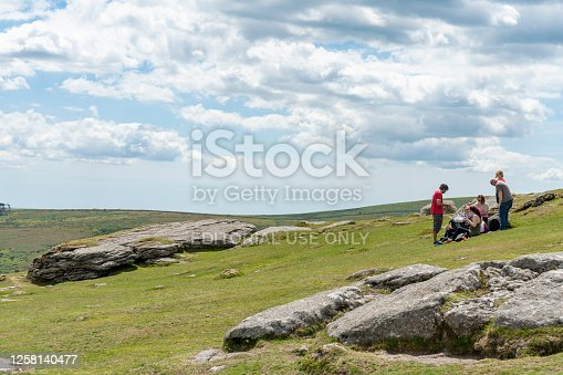 Haytor, near the B3387 . This is on South Dartmoor, Cornwall, England, UK. There is a family having a picnic in the shadow of the Tor rock formation.