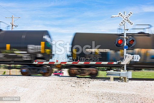Railway level crossing on rural road with safety sign, flashing red lights and barrier as a tank train passes while SUV waits.  Long exposure with crossing sign in sharp focus and train behind with motion blur.  In camera motion blur, horizontal, copy space.