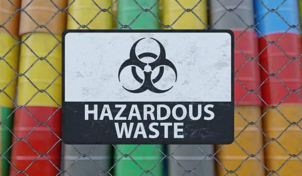 Hazardous waste sign on chain link fence. Oil barrels in background. 3D rendered illustration. stock photo