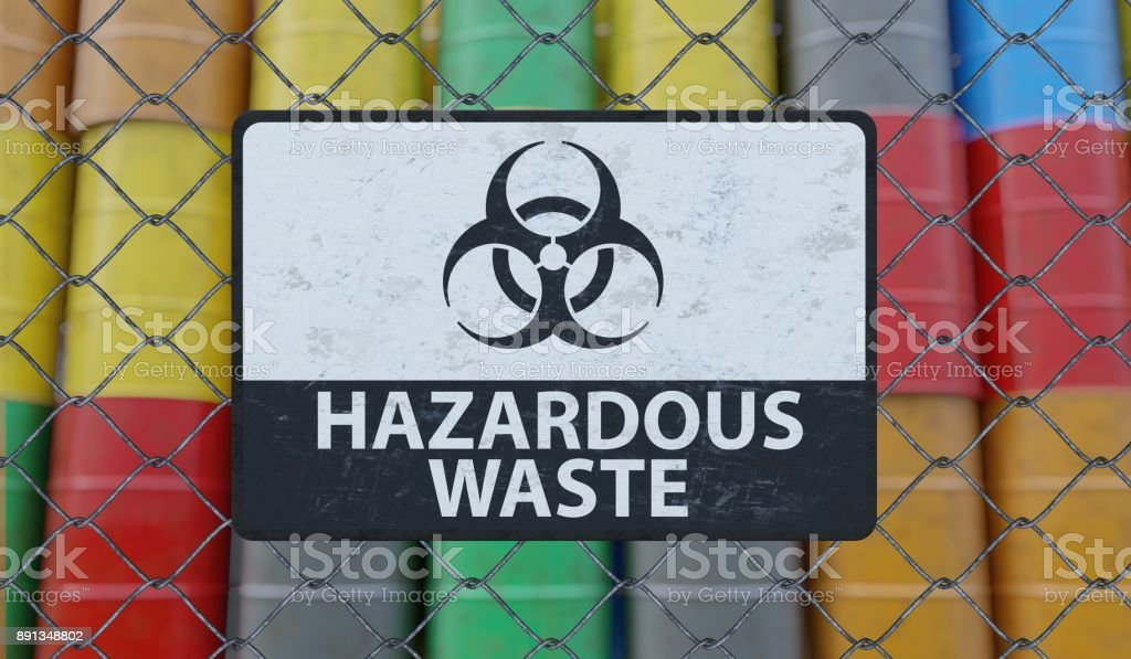 Hazardous waste sign on chain link fence. Oil barrels in background. 3D rendered illustration. stock photo