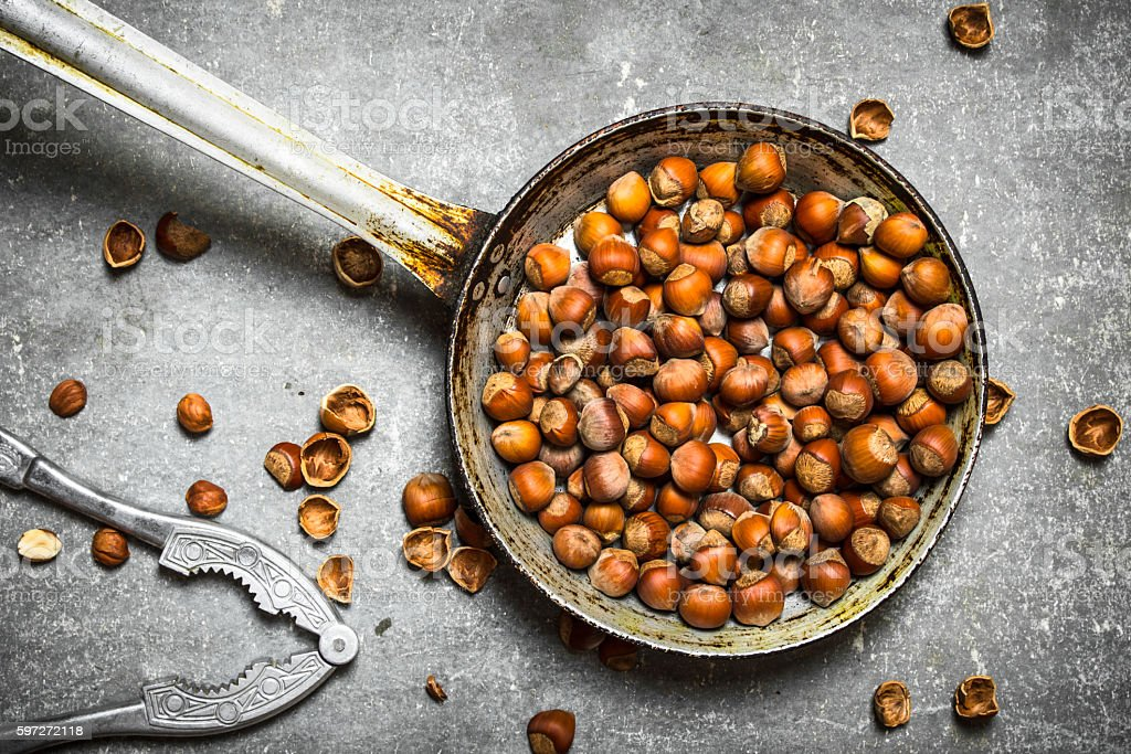 Hazelnuts and a Nutcracker in the old pan. royalty-free stock photo