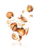 Hazelnuts crushed in the air close-up, isolated on white background