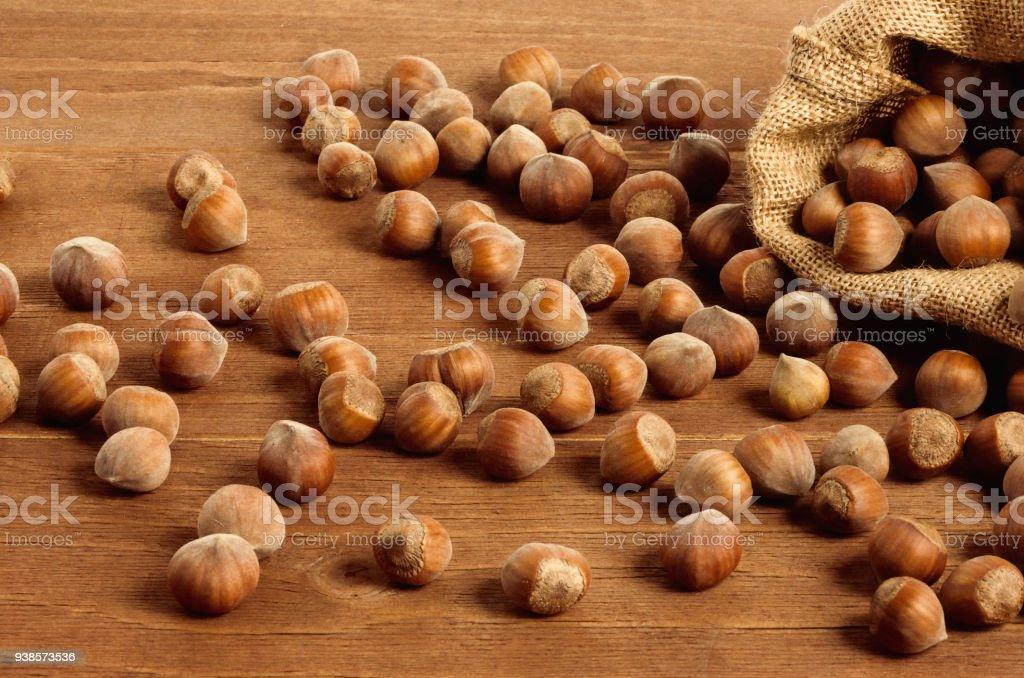 Hazelnuts in a yuta bag on wooden table - foto stock