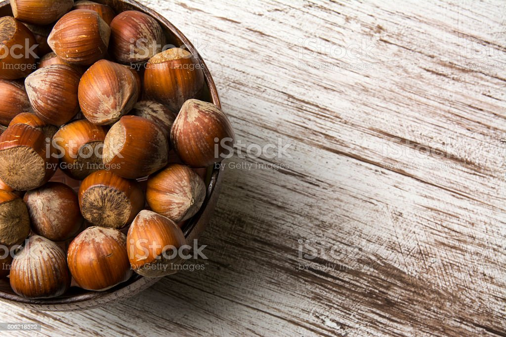 hazelnuts in wooden bowl on rustic background stock photo