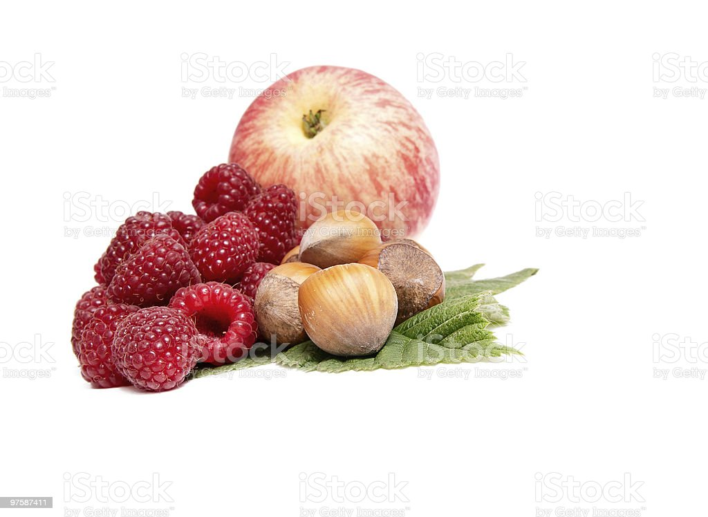 Hazelnuts,apple and raspberries on a white. royalty-free stock photo
