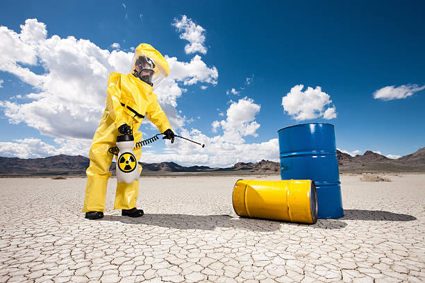 hazmat cleanup of oil barrels - white suit stock photos and pictures