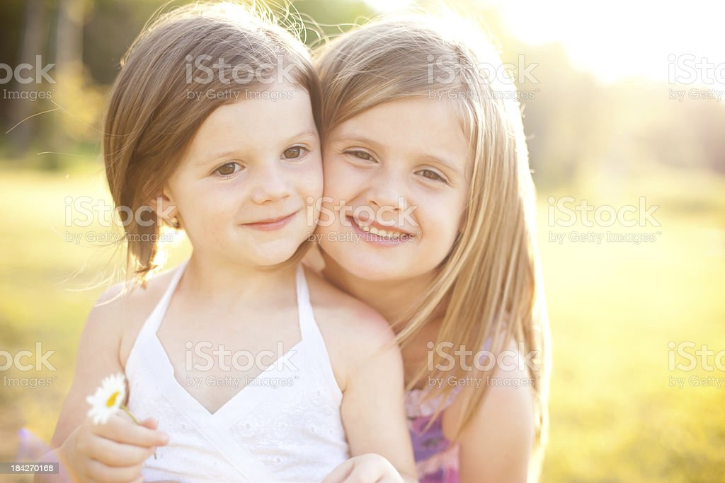 Hazy Backlit Image of Two Sister Smiling Together royalty-free stock photo