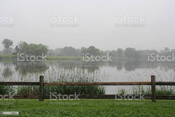 Photo of Hazy Rainy Day with Fence and Lake