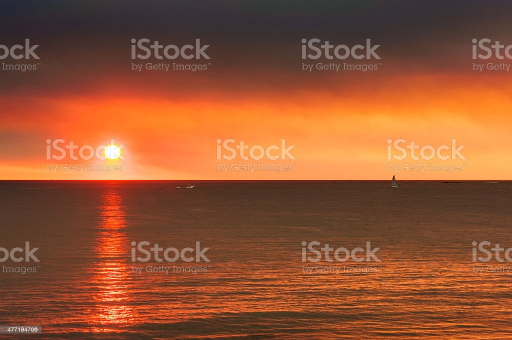 Hazy red ocean sunset with boats stock photo