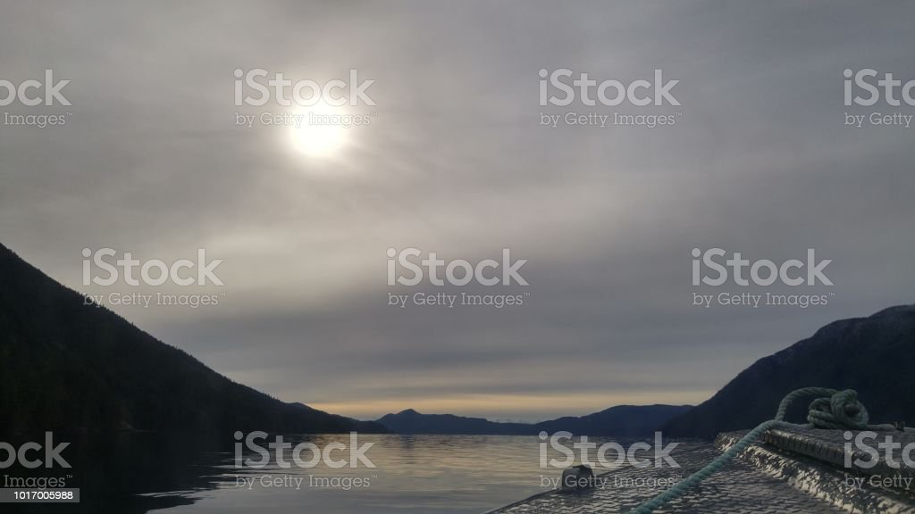 A hazy sky over calm waters sailing an inlet on the BC coast over the front of a boat stock photo