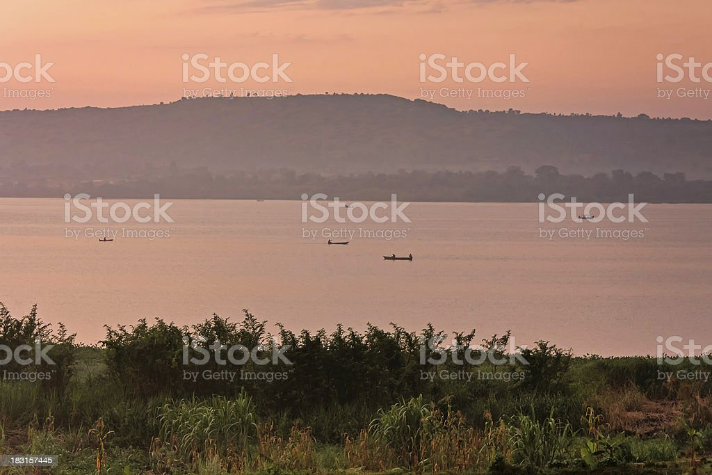Hazy view on Victoria Lake at dawn with fisher boats stock photo