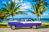 HDR-American blue classic car parked on the coastline near the beach in Havana Cuba - Serie Cuba Reportage