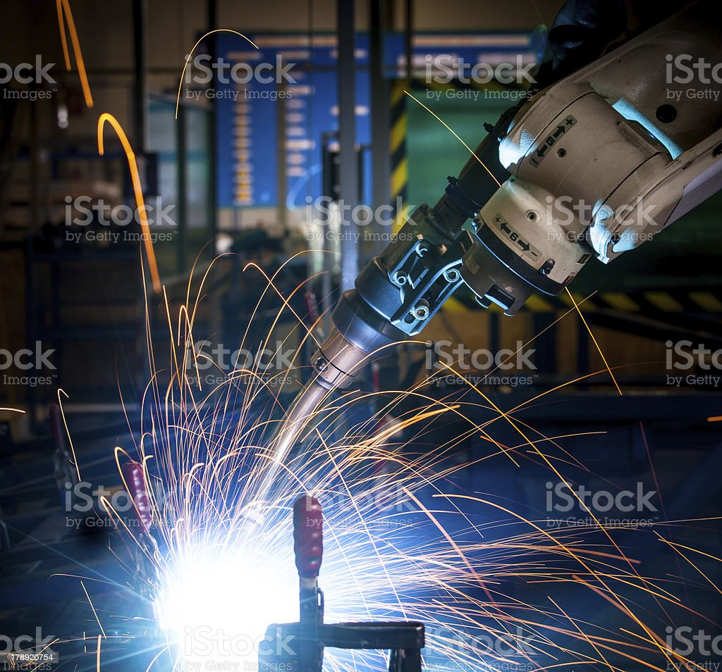 Robot arm welding uses torch to make sparks during manufacture of...