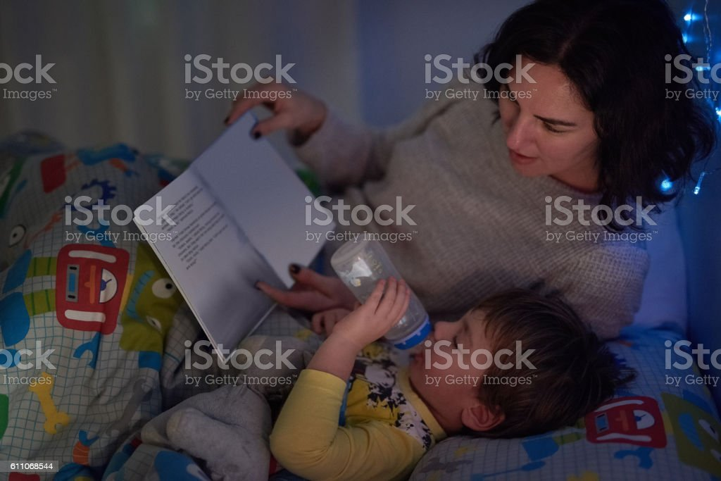 He always has his bottle and a book at bedtime stock photo