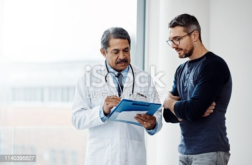 Shot of a confident mature male doctor consulting a patient  inside a hospit