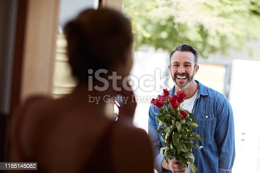 Cropped shot of an attractive mature man surprising his girlfriend with a bouquet of roses