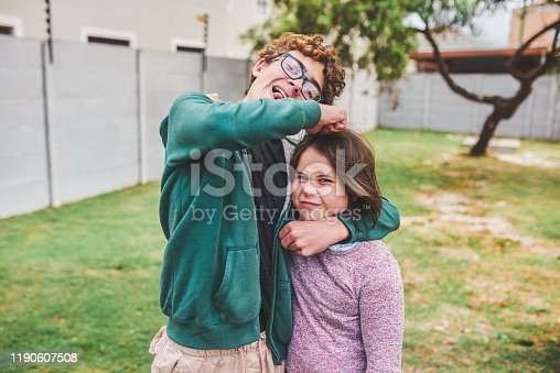 Shot of a young girl and her older brother playing together outside