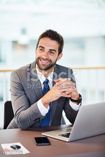 Shot of a young businessman working on a laptop in an office