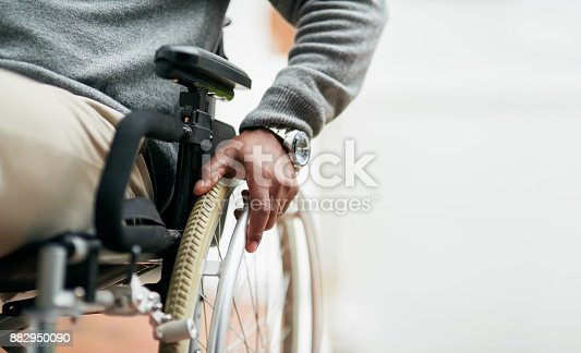 Cropped shot of an unrecognizable senior man sitting in his wheelchair at home