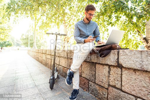 Young caucasian man with his electric scooter enjoying beautiful summer day outside while working on his laptop