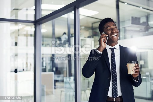 Shot of a young businessman talking on a cellphone in an office