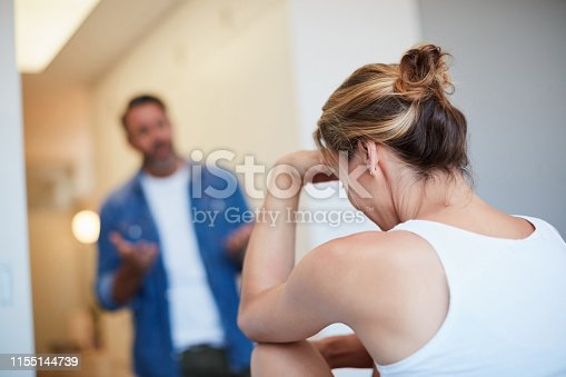 Rearview shot of an unrecognizable young woman looking distressed with her husband in the background