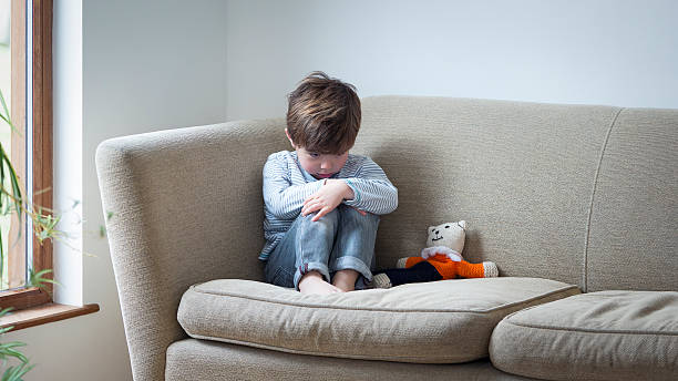 He doesn't feel safe in his own home Little boy suffering from child abuse curled up on the sofa with his teddy. teddy bear stock pictures, royalty-free photos & images